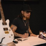 Dave Navarro doing the signing thing in the PRS booth, signature model at his side
