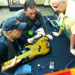 Dave Hinson, Drew Winn, and Mike Gutierrez inspecting a '57 P-Bass at Heritage Auction's booth.