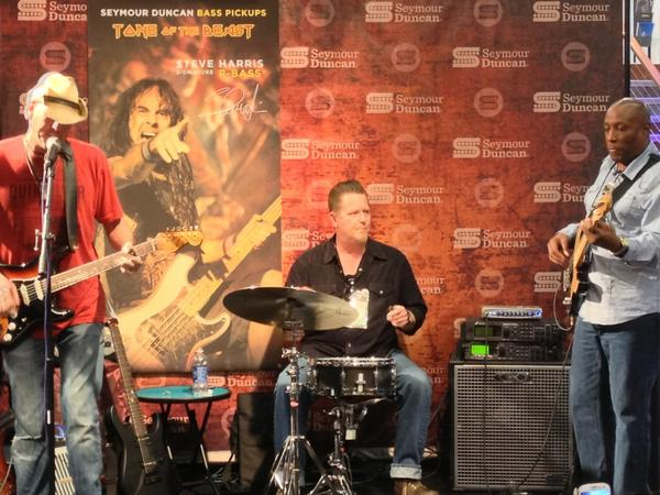 Johnny Hawthorne Trio performing at the Seymour Duncan booth.