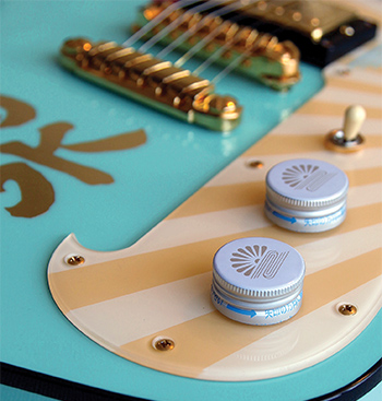 "Inspired by design elements from a bottle of sake, this guitar uses bottle caps for knobs and has gold-leaf kanji symbols, sun-ray pickguard, and traditional water-and-chrysanthemum symbols to complete the look. Gilbert calls the neck a ""massive baseball bat."""
