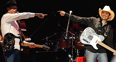 Owens with Brad Paisley during a 75th birthday bash for Owens. Paisley presented Owens with a custom-made black-and-silver-paisley Bill Crook guitar.
