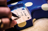 Fender Master Builder Paul Waller signing the neck pocket of Buddy Guys's personal Strat.