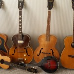 "Long-time reader who loves the old Harmony guitar line. Each of these was rescued from the trash heap and, if not pristine and beautiful, are now playable, great-sounding old friends. From left: H1203 Sovereign, 1964 H39 Hollywood with DeArmond pup, 1940 Patrician ""Nu Tone,"" Harmony 1260 Sovereign. Resting in front are a 50's-era H162 'terz' and a H410 Monterey mandolin"